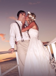 Wedding couple kissing aboard the Leilani yacht on a private sunset cruise.