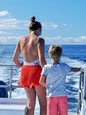 Mother and son enjoying the beautiful view over the wake of the Leilani yacht.