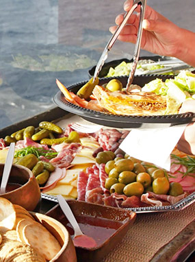 Serving food from a fresh buffet of olives, cheese, and meat.