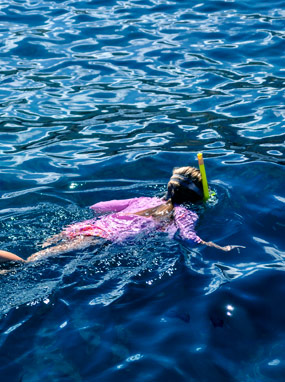 Kid snorkeling at the surface of ocean with bright reflections.
