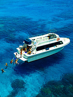Leilani Yacht anchored with tourists swimming and snorkeling off the stern.