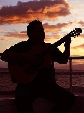 Silhouette of Hawaiian guitarist playing music on the Leilani yacht with the sun setting over the ocean behind him.