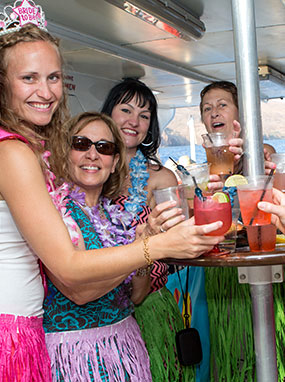 Women on the Leilani yacht making a toast with tropical drinks.
