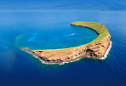 Aerial photo of Molokini Crater and the Leilani boat in the distance with deep blue Pacific ocean in Hawaii.