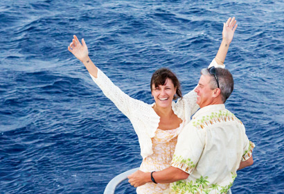 Woman with arms outstretched in joy with her partner on a romantic Leilani Yacht cruise.