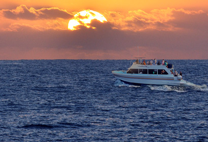 The Leilani yacht cruising past the Maui, Hawaii setting sun.